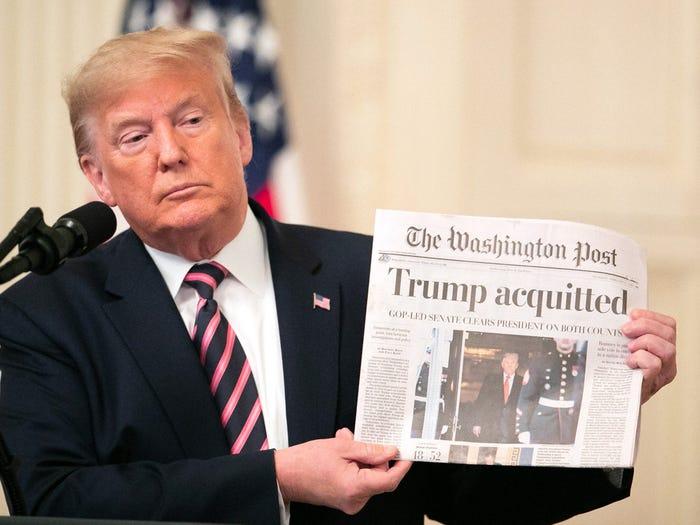 Дональд Трамп держит газету после того, как он был оправдан по двум статьям об импичменте